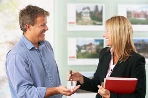 realtor handing house keys to new home owner